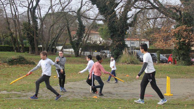 Des élèves sont sur le terrain en train de pratiquer le cricket